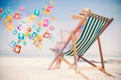 Zusammengesetztes Bild der Frau im sunhat, das auf Strand im Klappstuhl unter Verwendung des Tabletten-PC sitzt Stockbilder