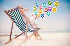 Zusammengesetztes Bild der Frau im sunhat, das auf Strand im Klappstuhl unter Verwendung des Tabletten-PC sitzt Stockfotografie