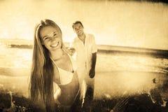 Zusammengesetztes Bild der Frau lächelnd an der Kamera mit dem Freund, der ihre Hand hält Lizenzfreie Stockfotos