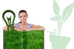 Zusammengesetztes Bild der Frau mit Rasenbuch Stockfotografie