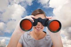 Zusammengesetztes Bild der Frau schauend durch Ferngläser Lizenzfreie Stockfotografie