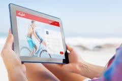 Zusammengesetztes Bild der Frau sitzend auf Strand im Klappstuhl unter Verwendung des Tabletten-PC Lizenzfreies Stockbild