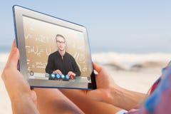 Zusammengesetztes Bild der Frau sitzend auf Strand im Klappstuhl unter Verwendung des Tabletten-PC stockbilder