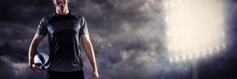 Zusammengesetztes Bild der Ganzaufnahme des lächelnden Rugbyspielers im schwarzen Trikot, das Ball hält stockfotografie