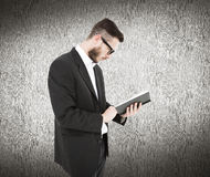 Zusammengesetztes Bild der geeky Lesung des jungen Mannes vom Schwarzbuch Stockfoto