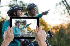 Zusammengesetztes Bild der geernteten Hand, die digitale Tablette hält Lizenzfreie Stockfotografie
