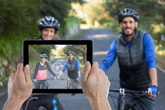 Zusammengesetztes Bild der geernteten Hand, die digitale Tablette hält Stockbilder