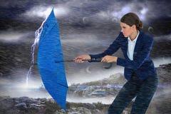 Zusammengesetztes Bild der Geschäftsfrau blauen Regenschirm halten Lizenzfreie Stockfotos