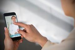 Zusammengesetztes Bild der Geschäftsfrau, die Handy verwendet Lizenzfreie Stockbilder