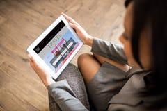 Zusammengesetztes Bild der Geschäftsfrau, die Tablette verwendet Stockfotos