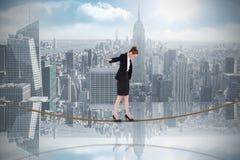 Zusammengesetztes Bild der Geschäftsfrau einen Balanceakt auf Drahtseil durchführend Lizenzfreie Stockfotos
