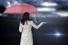 Zusammengesetztes Bild der Geschäftsfrau Regenschirm halten Stockfoto
