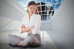 Zusammengesetztes Bild der gestörten Geschäftsfrau, die mit den Armen gekreuzt sitzt Lizenzfreies Stockbild