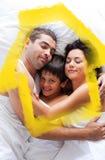 Zusammengesetztes Bild der glücklichen Familie liegend im Bett Stockfoto