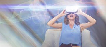 Zusammengesetztes Bild der glücklichen Frau, die Gläser der virtuellen Realität beim Sitzen auf Sofa verwendet Lizenzfreie Stockfotografie