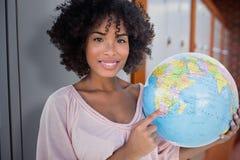 Zusammengesetztes Bild der glücklichen Frau zeigend auf Kugel Lizenzfreies Stockfoto