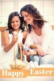 Zusammengesetztes Bild der glücklichen Mutter und der Tochter, die Ostereier hält lizenzfreie abbildung