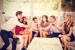 Zusammengesetztes Bild der Gruppe Freunde, die Getränke rösten und haben Lizenzfreie Stockbilder