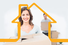 Zusammengesetztes Bild der hübschen Frau Kästen in ihrem neuen Haus halten Lizenzfreies Stockfoto