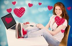 Zusammengesetztes Bild der hübschen Rothaarigen mit Füßen oben auf Schreibtisch Lizenzfreie Stockfotos