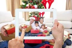 Zusammengesetztes Bild der Hand Tabletten-PC halten stockbild