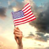 Zusammengesetztes Bild der Handwellenartig bewegenden amerikanischer Flagge lizenzfreies stockbild