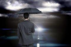 Zusammengesetztes Bild der hinteren Ansicht des noblen Geschäftsmannes grauen Regenschirm halten Stockbilder