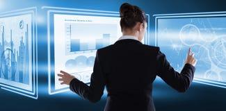 Zusammengesetztes Bild der hinteren Ansicht der Geschäftsfrau, die fantasiereichen digitalen Schirm verwendet lizenzfreie stockfotos