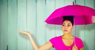 Zusammengesetztes Bild der jungen Frau rosa Regenschirm tragend Lizenzfreie Stockbilder