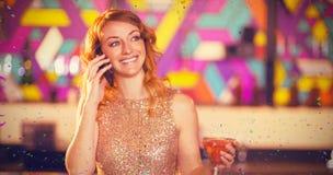 Zusammengesetztes Bild der jungen Frau sprechend am Handy beim Haben des Cocktails am Zähler Lizenzfreie Stockfotografie