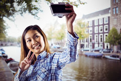 Zusammengesetztes Bild der lächelnden asiatischen Frau, die Foto mit Kamera macht Lizenzfreies Stockbild