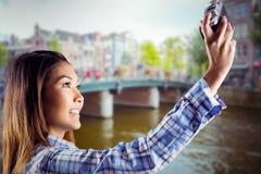 Zusammengesetztes Bild der lächelnden asiatischen Frau, die Foto mit Kamera macht Stockfoto