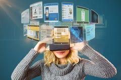 Zusammengesetztes Bild der lächelnden blonden Frau, die Kopfhörer 3d der virtuellen Realität verwendet Lizenzfreie Stockfotos