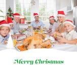 Zusammengesetztes Bild der lächelnden Familie um den Abendtisch am Weihnachten Lizenzfreies Stockfoto