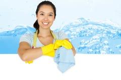 Zusammengesetztes Bild der lächelnden Frau lehnend auf weißer Oberfläche Lizenzfreies Stockfoto
