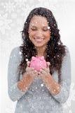 Zusammengesetztes Bild der lächelnden Frau Sparschwein in ihren Händen betrachtend Lizenzfreies Stockfoto