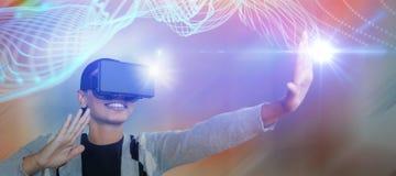 Zusammengesetztes Bild der lächelnden jungen gestikulierenden Frau beim Tragen von Gläsern der virtuellen Realität Stockfotos