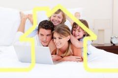 Zusammengesetztes Bild der liebevollen Familie einen Laptop betrachtend, der sich auf Bett hinlegt Lizenzfreie Stockfotografie