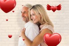 Zusammengesetztes Bild der liebevoller Paarstellung und -c$umarmens Stockfotografie