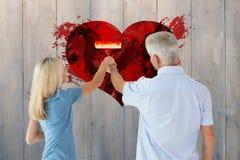 Zusammengesetztes Bild der Malereiwand des glücklichen Paars mit Rolle Stockbild