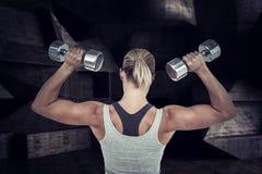 Zusammengesetztes Bild der muskulösen Frau ausarbeitend mit Dummköpfen Lizenzfreies Stockfoto