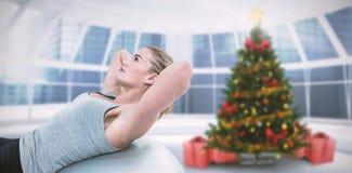 Zusammengesetztes Bild der muskulösen Frau, die das Handeln sitzt, ups auf Übungsball Lizenzfreies Stockbild
