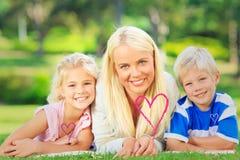 Zusammengesetztes Bild der Mutter mit ihren Kindern, die sich während des Sommers hinlegen Stockfotos