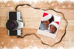 Zusammengesetztes Bild der Mutter und der Tochter, die ein Weihnachtsgeschenk öffnen lizenzfreies stockfoto