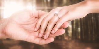 Zusammengesetztes Bild der Nahaufnahme des Paarhändchenhaltens Lizenzfreies Stockbild