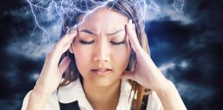 Zusammengesetztes Bild der nervösen Geschäftsfrau ihren Kopf halten Lizenzfreie Stockfotografie