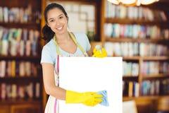 Zusammengesetztes Bild der netten Frau abwischend hinunter weiße Oberfläche Lizenzfreies Stockfoto
