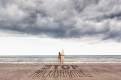 Zusammengesetztes Bild der ruhigen Frau im Bikini mit Surfbrett auf Strand Stockbild