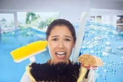 Zusammengesetztes Bild der sehr betonten Frau mit Reinigungswerkzeugen Stockbilder