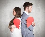 Zusammengesetztes Bild der Seitenansicht der jungen Paare, die defektes Herz halten Lizenzfreie Stockfotografie